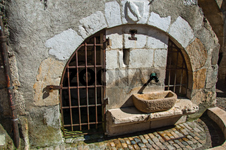 Old stone water fountain with iron gates at Annecy