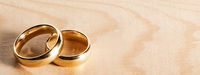 Golden wedding rings on wood