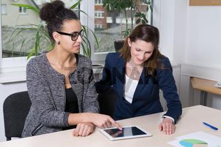 Eine Frau zeigt einer anderen etwas auf dem Tablet