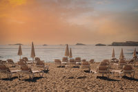 Parasols and deckchairs on beach during sunset. Ibiza