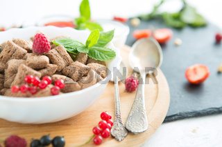 healthy breakfast cereal with fruit on the summer table with a white tablecloth Healthy tasty breakfast chocolate square pads with strawberries, raspberries, black currants and red currants.