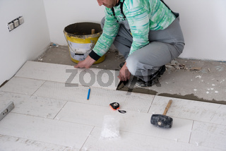 worker installing the ceramic wood effect tiles on the floor