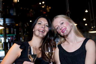 Two happy female friends toasting with champagne