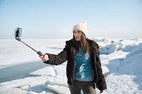 Female traveler at Jokulsarlon Glacial Lagoon using monopod to make selfie picture