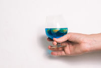 Glass goblet with cocktail on a white background. The glass is held by a woman's hand. An alcoholic drink of blue color and slices of mandarin.