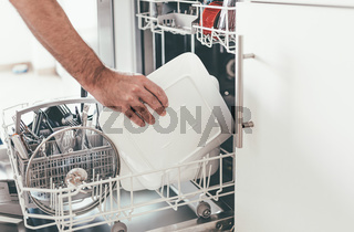 person emptying or loading dishwasher in kitchen