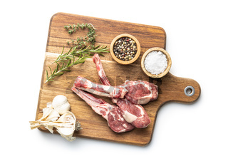 Slices raw lamb chops with salt, pepper and rosemary on cutting board