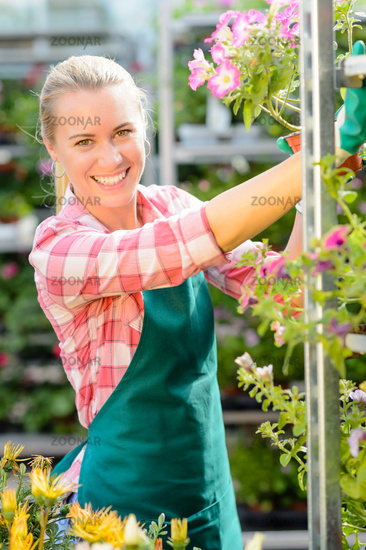 Smiling garden center woman working potted flowers