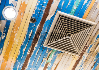 Air conditioner mask and  lighting On the ceiling that decorated with old wooden panels and peeling paint