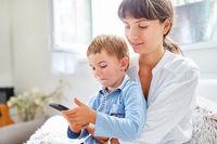 Kind spielt mit Smartphone neben Mutter