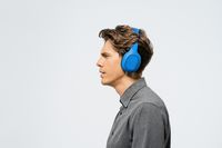 Portrait of a young guy in grey outfit standing sideways listening music wearing blue wireless headphones. Funny young guy listen to his favourite track or song