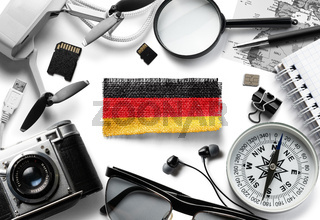 Flag of Germany and travel accessories on a white background.