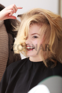 Beautiful smiling girl with blond wavy hair by hairdresser. Hairstylist combing female client. Young woman in hairdressing beauty salon. Hairstyle.