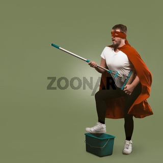 Superhero has fun with cleaning equipment. Man in red cape holds mop and presents himself as musician with guitar. Isolated on green background. Template with copy space at left side