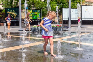 Girl playing with water fountains on square downtown Eger, Hungary