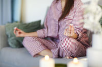 Young girl with cup of hot beverage and candles sitting on the sofa
