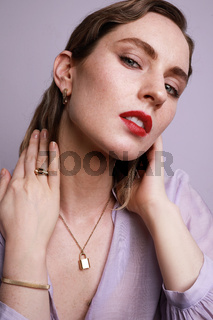 Caucasian young woman wearing golden jewellery posing on colourful wall. Vertical close-up of beautiful woman.