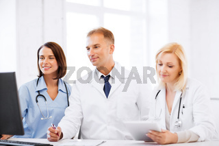 doctors looking at computer on meeting