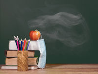 Back to virtual school background concept with stack of books and apple with face mask