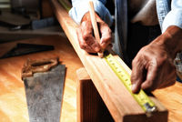 Closeup of a woodworker in his workshop marking a board for cutting.