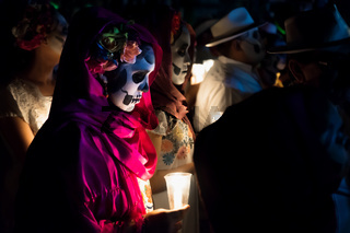 Close up of customed women dressed as Catrinas with skull make-up holding candles at the event for dias de los muertos at the Festival Des Las Animas at the Cementerio General, Merida, Mexico
