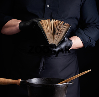 male cook in a black uniform holds an old cookbook with recipes, on a table is a cast-iron frying pan with a wooden handle