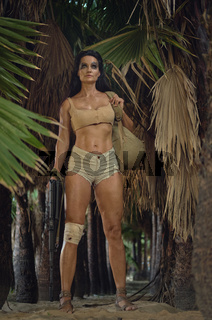 Athletic woman holding gun posing in palm trees forest