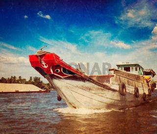 Vintage retro hipster style travel image of boat on Mekong river delta