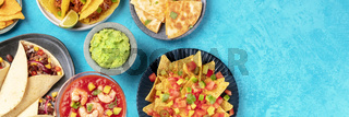 Mexican food panoramic top shot with copy space, a flat lay on a blue background. Nachos, guacamole, shrimp cocktail, burritos, quesadillas with a place for text or logo
