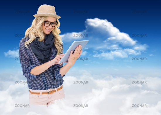 Composite image of smiling trendy blonde using tablet computer