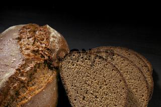 Sliced black bread on wooden table