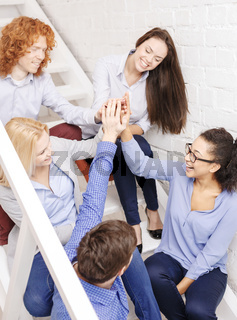 team doing high five gesture sitting on staircase