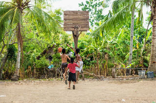 Three kids playing basketball at sand field with old wooden basketball basket, Siquijor, Philippines