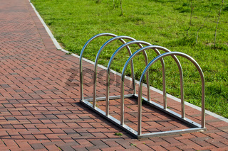 Modern Parking for bicycles made of stainless steel on the background of paving slabs
