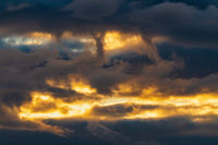 Beautiful dramatic clouds in sky illuminated by rays of sun at sunset to change weather