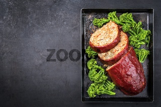 Traditional American meatloaf from ground beef with ketchup and broccoli as top view on a rustic metal tray with copy space left