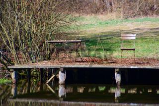 Angefaulter Holzsteg am Wasser mit antiken Möbeln
