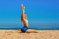 Young blonde woman practicing yoga on beach