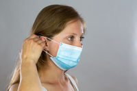 Young blond woman attaching surgical mask to her face