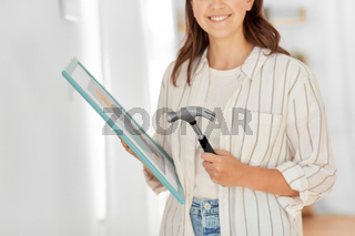 woman with hammer and picture in frame at home