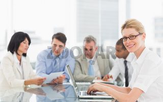 Businesswoman using her laptop during a meeting looking at camera