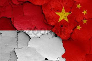 flags of Indonesia and China painted on cracked wall