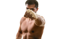 Young muscular strong man with bandaged raised fist, isolated on white background. Martial arts, fitness, workout concept.