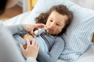 mother with nasal spray treats sick daughter
