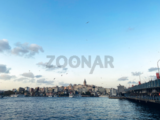 The Galata Bridge and the Galata Tower on the Bosphorus in Istanbul, Turkey. Istanbul views with many seagulls and cloudy sky. Karakoy district and Golden Horn