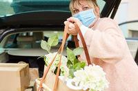 Frau mit Mundschutz hält Tasche vor Kofferraum