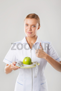 Healthy eating or diet concept. Smiling woman doctor with a green apple and measuring tape.