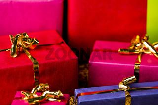Vier goldene Schleifen um verpackte Geschenke