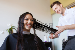 happy woman with stylist cutting hair at salon