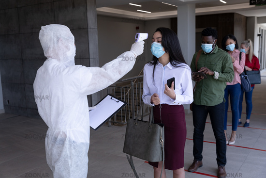 Health worker wearing protective clothes checking temperature of businesswoman